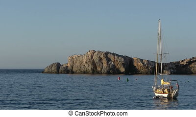 small sailboat beside the large rock
