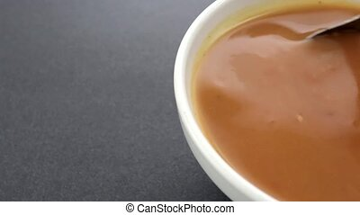Stirring tomato soup - Video of a bowl of tomato bisque soup...