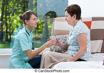 Giving patient a glass of water - Nurse giving patient a...