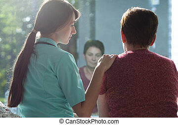Cheering up - Young attractive nurse cheering up ill woman