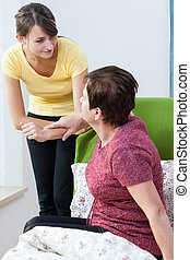 Help to stand up - Young pretty therapist helps her patient...