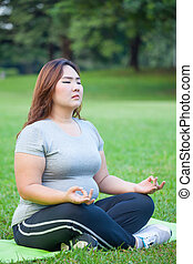 Plus size woman practicing yoga - Plus size asian woman...