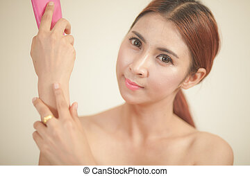 asian girl applying moisturizer