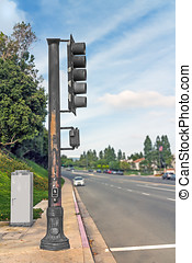 Side view of metal stoplight pole at suburban crosswalk -...