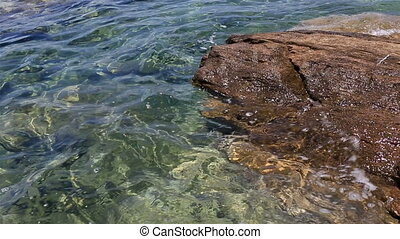 Clear water of Aegean Sea washes the rocks on shore.