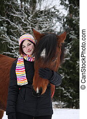 Beautiful teenager girl hugging brown horse in winter forest