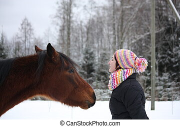 Beautiful teenager girl playfully kissing brown horse in...