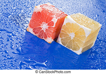 Citrus cubes on blue surface - Red and yellow citrus cubes...