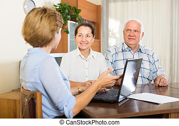 Senior couple with social worker at home - Senior couple...