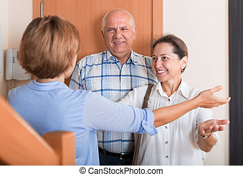 Meeting friends - Woman meeting mature friends at the door