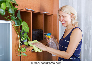 Mature woman dusting wooden furniture - Mature smiling woman...