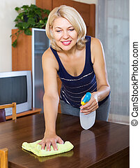 Smiling houswife dusting wooden furniture with rag and...