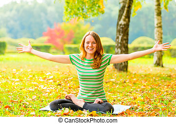 cheerful slim girl does yoga and laughs