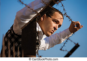 Man behind a barbed wire