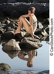 Depressed Woman Sitting On Rock - Portrait Of Young Woman...