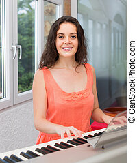 Young woman playing piano at home and smiling
