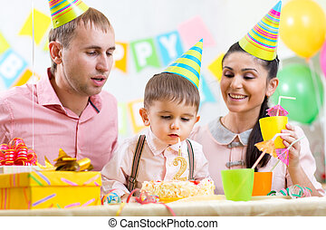 kid with family blowing candle on birthday cake - kid boy...