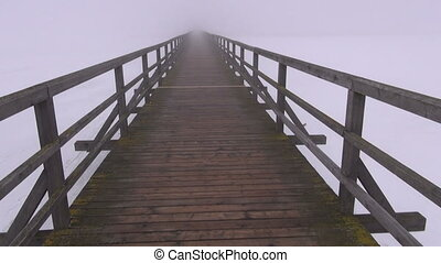winter fog and wooden bridge - walking on empty old wooden...