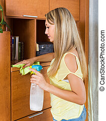 girl cleaning furniture with cleanser and rag in living room...