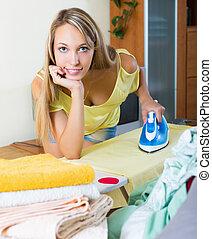 Blonde girl ironing with iron - Smiling blonde girl ironing...