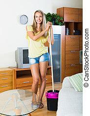 Blonde girl washing parquet floor