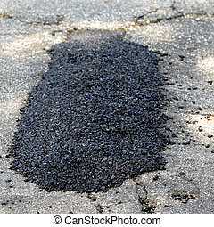 Pothole Patch - Repaired pothole with a black tarmac