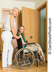 Woman helping handicapped girl - Smiling elderly mother...