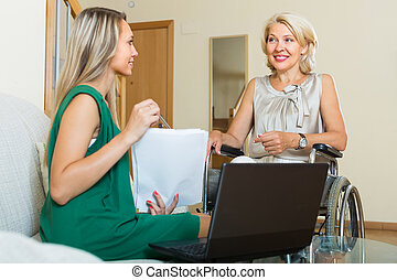 Social worker and handicapped woman with laptop - Social...