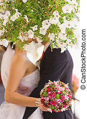 bridal bouquet in hands of kissing bride and groom