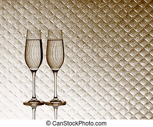 Two champagne glasses on blurred checkered background, close...