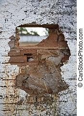 Hole in crumbling wall