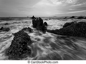 splashing wave with beautiful sunset in black and white