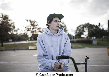 Portrait of young bmx rider in autumn with sweater on