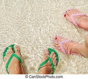 Colorful flip flops on translucent ocean water - close up of...