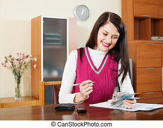 housewife calculates the family budget - brunette housewife...