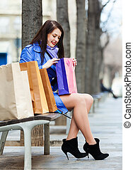 woman   with purchases at bench