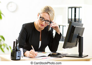 middle-aged business woman working in office and talking on phone
