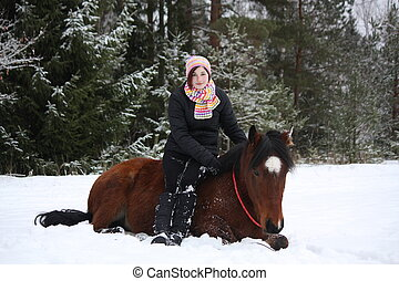 Teenager girl and brown horse lying in the snow in winter...