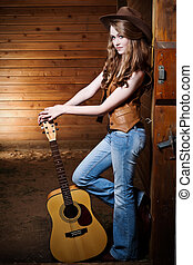 Beautiful caucasian cowgirl with guitar - A portrait of a...