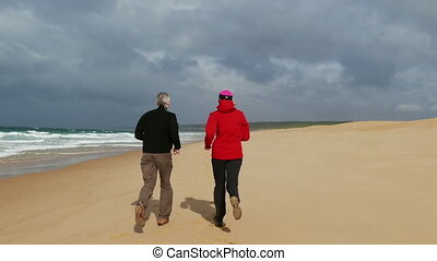 Middle-aged Couple Jogging on Beach - Middle-aged Couple...