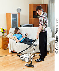 Man cleaning with vacuum cleaner - Man cleaning with vacuum...