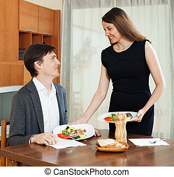 Loving woman serving dinner to beloved man at table