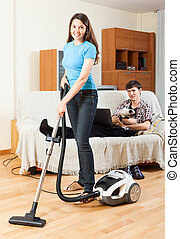 Girl doing floor cleaning while man resting over sofa - Girl...
