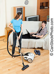 Girl doing room cleaning with vaccuum cleaner while man with...