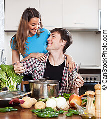 Happy man and woman cooking soup - Happy man and pretty...