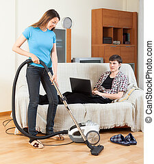 Girl doing room cleaning while man resting over sofa - Girl...