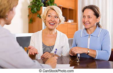 women consulting at insurance agent - Smiling senior women...