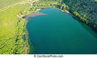 Brljan lake, aerial ascent shot - Copter aerial view of the...
