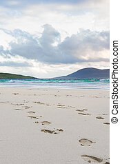 Footprints in the sand, turquise water and impressive skyes,...