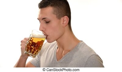 young man drinking a beer - Handsome boy drinking beer over...